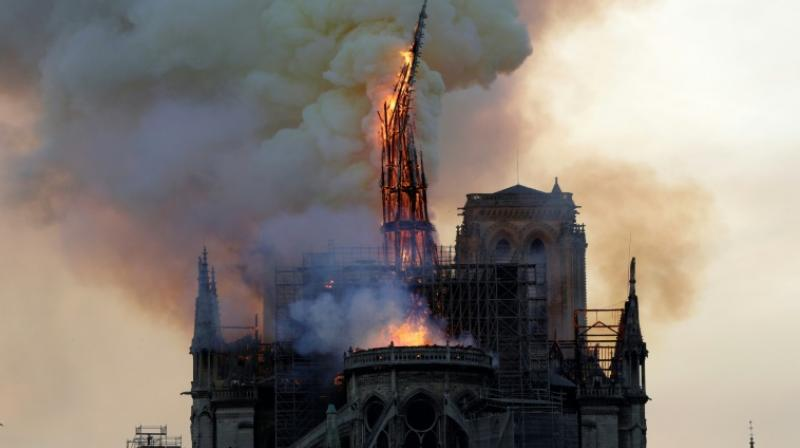 President Emmanuel Macron has vowed the emblematic monument will be rebuilt after its spire and roof collapsed Monday night in a blaze. (Photo: AFP)