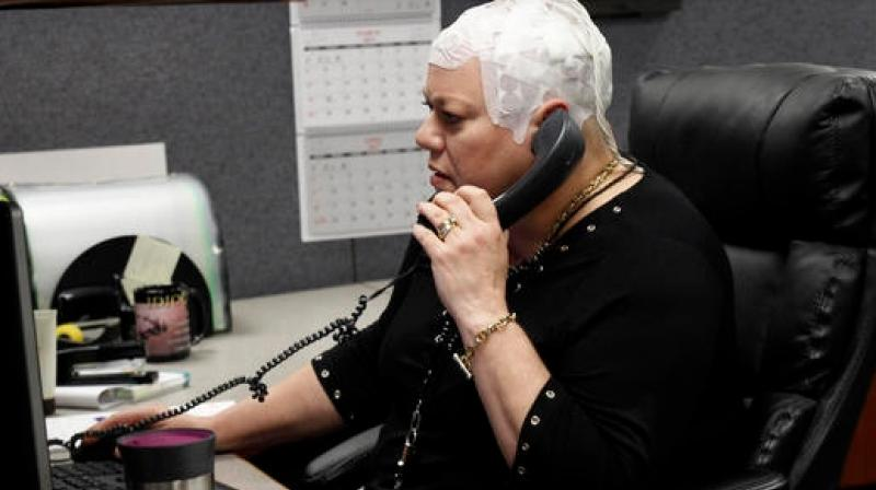 In this March 29, 2017 photo, Joyce Endresen wears an Optune therapy device for brain cancer, as she speaks on a phone at work in Aurora, Ill. She was diagnosed in December 2014 with Glioblastoma.  (Photo: AP)