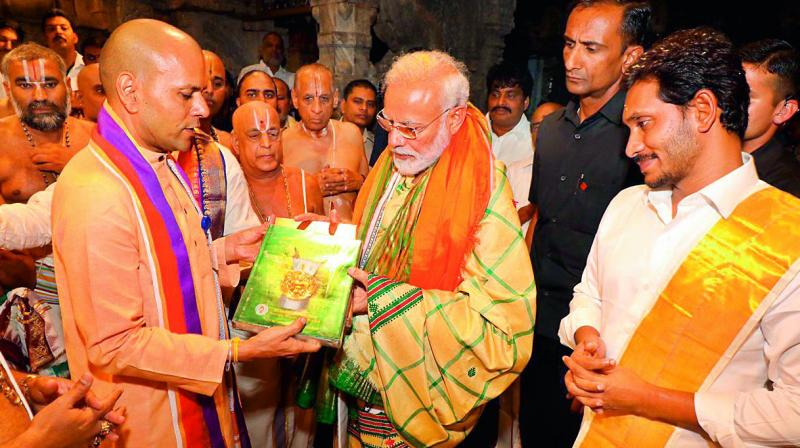 TTD executive officer Anil Kumar Singhal presents a book on antique coins to Prime Minister Narendra Modi at Lord Venkateswara temple during his visit to in Tirupati on Sunday.