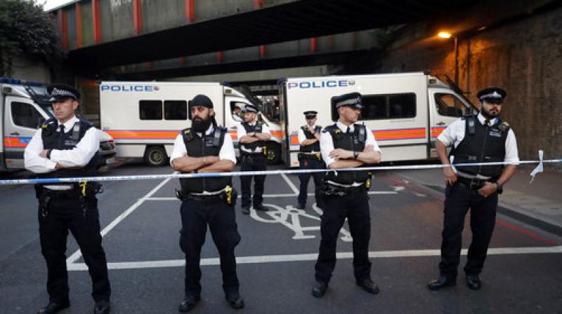 Police stand guard at a cordon on a road near Finsbury Park station after a vehicle struck pedestrians in north London. (Photo: AP)