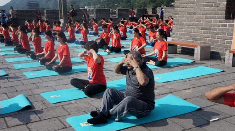 Minister of State for External Affairs VK Singh doing 'Bhramari Pranayam' (a breathing technique) along with others at The Great Wall of China, a day ahead of International Yoga Day, in Beijing on Tuesday. (Photo: AP)