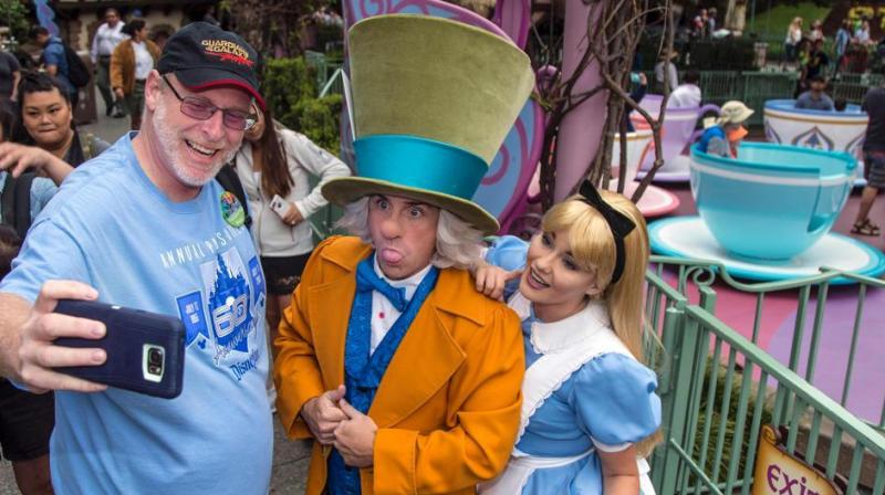 Jeff Reitz clicks a selfie with the Mad Hatter and Alice after a teacup ride at the Mad Tea Party in Fantasyland at Disneyland on June 22, 2017, during his 2,000th visit to the park in Anaheim, California. (Photo: AFP)