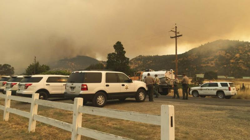 Merced and Mariposa County Sheriff's Office members gather during a wildfire in Mariposa County, California. (Photo: AP)