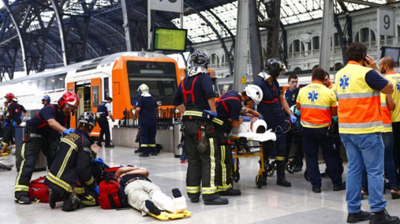 Injured passengers are attended to on the platform of a train station in Barcelona, Spain. Dozens of people were injured when a morning commuter train they were traveling on crashed into the buffers in a station in northeastern Barcelona early Friday. (Photo: AP)