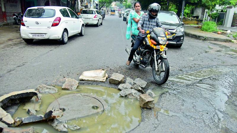 With the sewer manhole at Bholakpur in Musheerabad road broken, motorists are forced to wade through overflowing sewage. (Photo: S. Surender Reddy)
