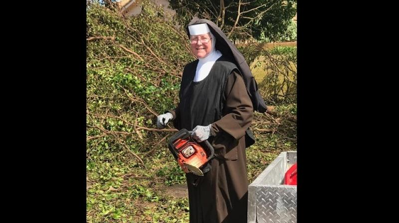 Sister Margaret Ann cutting down trees in Florida ollowing Hurricane Irma. (Photo: Facebook / Miami-Dade Police Department)