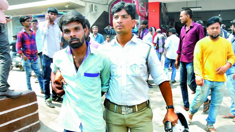 A cop arrests a person for selling tickets in black at one of the theaters at RTC crossroads during the Baahubali-2 release on Friday. (Photo: DC)