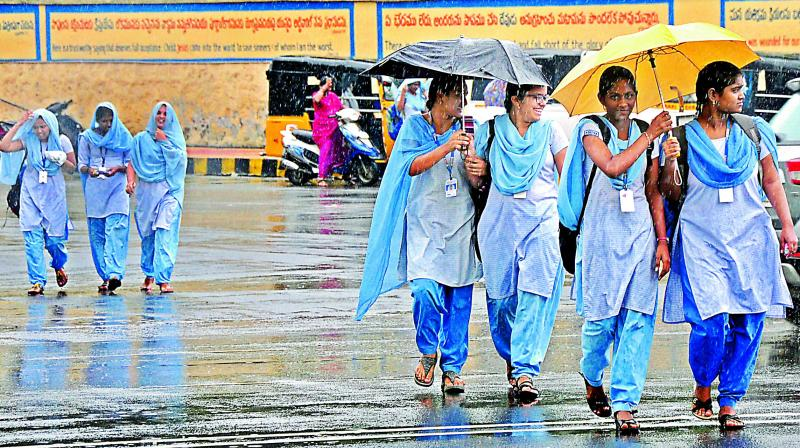 Schoolgirls shield themselves from the rain near Ramnagar in Visakhapatnam on Friday. The almost incessant rain is contributing to the seasonal fevers gripping the district. (Photo: P. Narasimha Murthy)