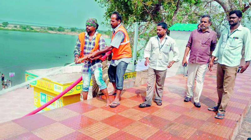 On the even of Mahasivaratri, civic workers clean up the Kotilingala ghat in Rajahmundry on Saturday for devotees. Devotees will throng the ghat to take a holy dip and perform rituals.  (DC)