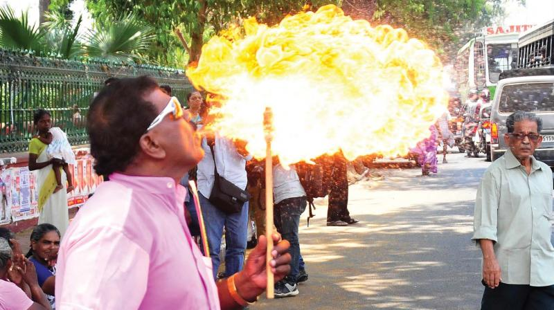 Dancer Thamby performs a fire act to support Congress president Rahul Gandhi who is contesting from Wayanad, in Thiruvananthapuram on Wednesday. (Photo: A.V. MUZAFAR)