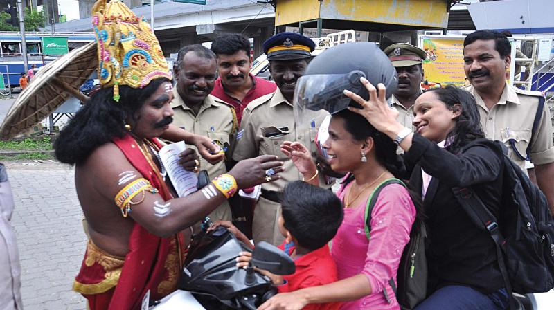 'Mahabali' takes part in the traffic awareness campaign of the traffic cops in Kochi telling a woman two-wheeler driver who was riding the scooter without a helmet, about the virtue of wearing helmets at Edappally Junction in Kochi. 	—DC FILE PIC