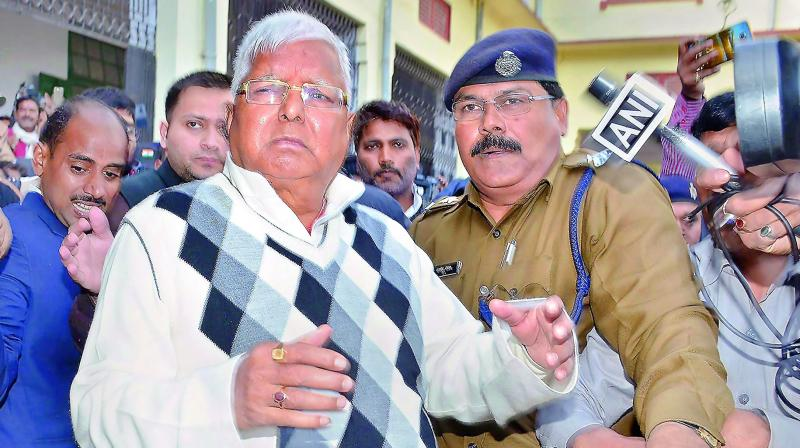 RJD supremo Lalu Yadav escorted by police after being convicted by the special CBI court in the fodder scam case, in Ranchi, on Saturday. 	(Photo: PTI)