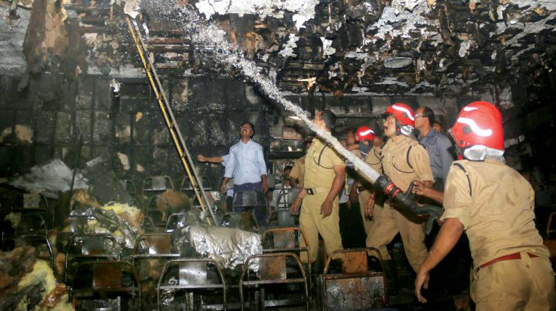 Fire force officials double-check burnt ceiling to ensure that the fire doesn't re-emerge from them at Padmanabha Theatre near East Fort on Thursday morning. (Photo: G.G. Abhijith)