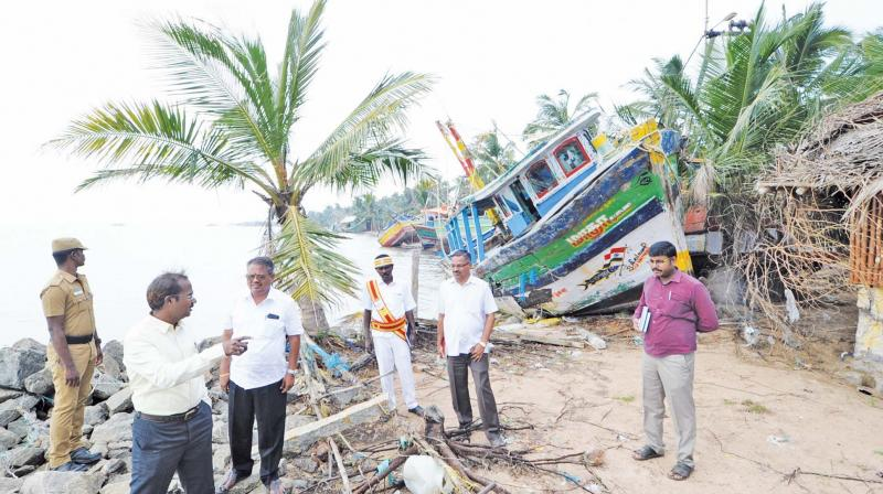 A. Annadurai, Thanjavur district collector, looking at a damaged boat after the cyclone at Sethubavachathiram.