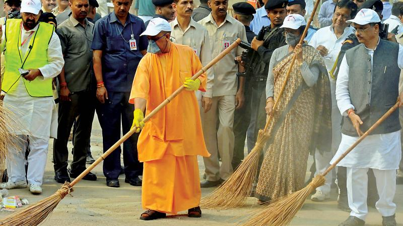 UP Chief Minister Yogi Adityanath wields a broom as he takes part in a cleanliness drive at the Taj Mahal in Agra on Thursday   (Photo: PTI )