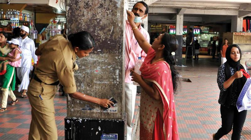 Police, merchants and students and teachers of Payyanakkal Government Vocational Higher Secondary School clean the premises of Mofussil bus stand on Sunday. (Photo: DC)