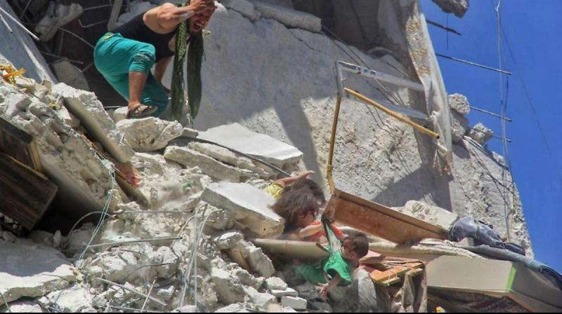 The picture went viral on social media networks: two dust-covered Syrian girls, trapped in rubble, grab their baby sister from her shirt as she dangles from a bombed-out building. (Photo: AFP)