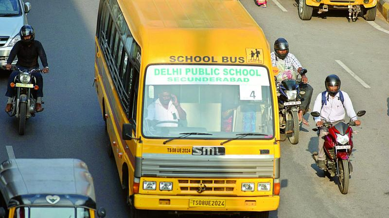 A school bus driver talks over phone while driving on a busy Begumpet road on Wednesday. (Photo: S. Surender Reddy)