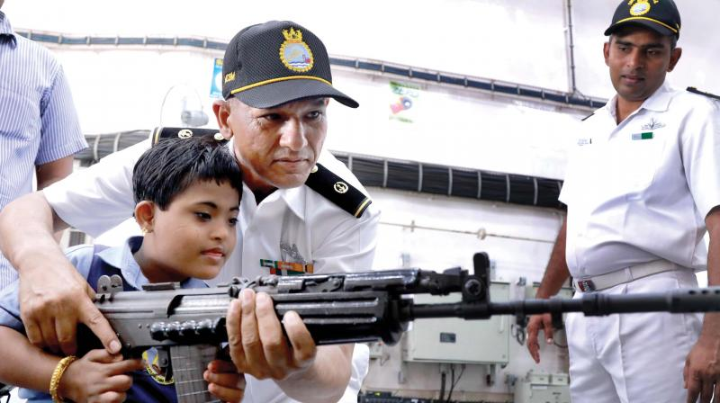 Navy personnel explains functioning of an INSAS rifle to a special child on board INS Sunayna in the Southern Naval command as part of the Navy week celebrations in Kochi on Wednesday. (Photo: ARUN CHADRABOSE)
