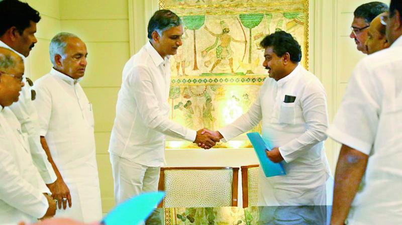Telangana and Karnataka ministers T. Harish Rao and M.B. Patil exchange files after their meeting in Hyderabad on Thursday. (Photo: DC)