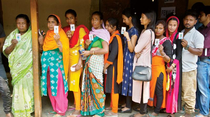 Voters show their voter identity card as they stand in line to vote (Photo :AP)