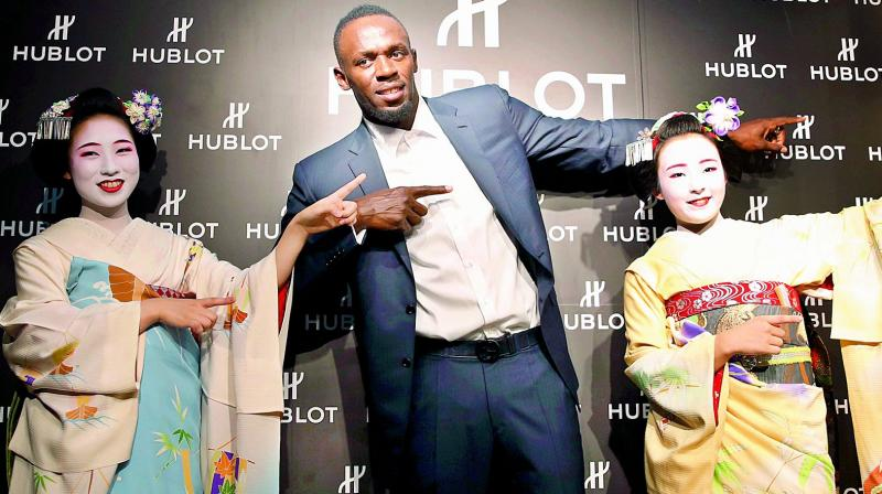 Usain Bolt of Jamaica gestures with maiko, or an apprentice geisha, during a promotional event in Kyoto, western Japan on Tuesday. (Photo: AP)
