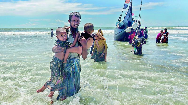 A Rohingya Muslim man walks to the shore carrying two children after they arrived on a boat from Myanmar to Bangladesh in Shah Porir Dwip (Photo: AP)
