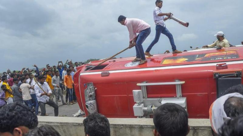 Pro-reservation outfits of Maratha community burn a vehicle after a clash with the police personnel. (Photo: PTI)
