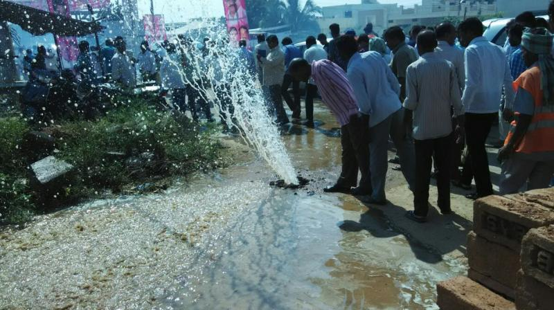 Curious onlookers see water spouting from an old pipeline at Uppal, near the venue of a function to inaugurate a new project, in Hyderabad on Friday.