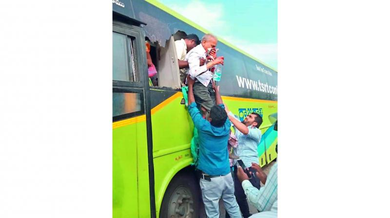 Bystanders help a passenger out of a bus that was involved in a collision with three lorries.