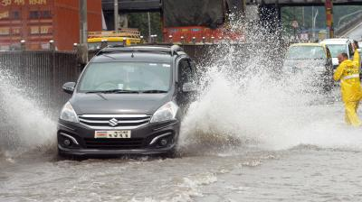 Car wade through flooded street in Mumbai. (Photo: Rajesh Jadhav)