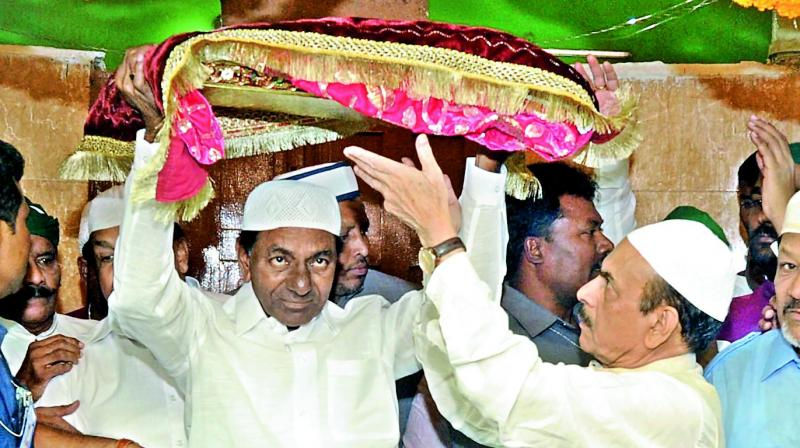 Chief Minister K. Chandrasekhar Rao offers a chaddar at the Jahangir Peer dargah at Kothur in Rangareddy district, assisted by Deputy CM Mahmood Ali.