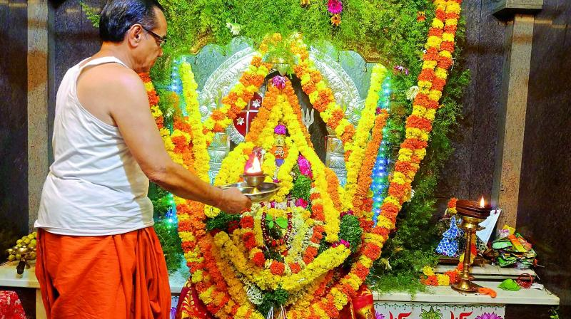 The temple priest performs rituals to the idol almost fully covered by floral decorations. (Photo: P. Surendra)