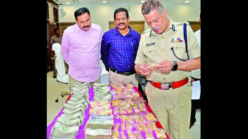 Police commissioner Ch. D. Tirumala Rao look at the seized cash and gold in Vijayawada on Saturday. (Photo: DC)