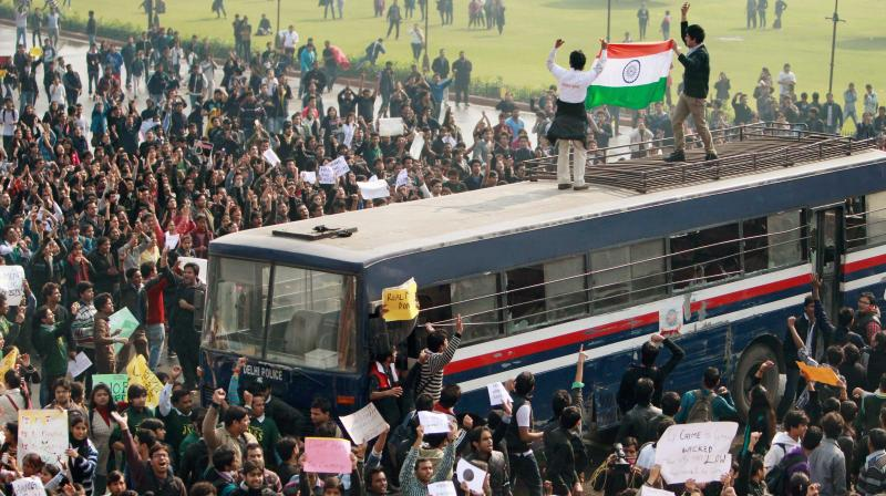 Protesters, atop a police bus, hold national flag during a demonstration at Vijay Chowk in New Delhi. (Photo: PTI/File)