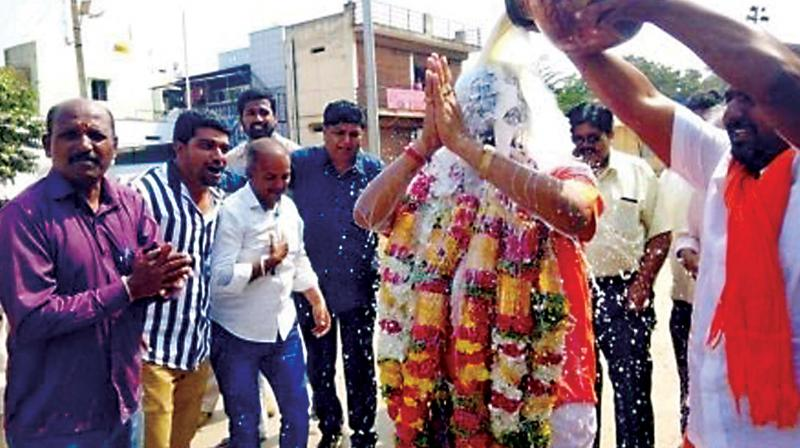 Supporters of BJP rebel  Kaviraj Urs pour milk on him soon after he filed his nomination papers for the Vijayanagara seat.