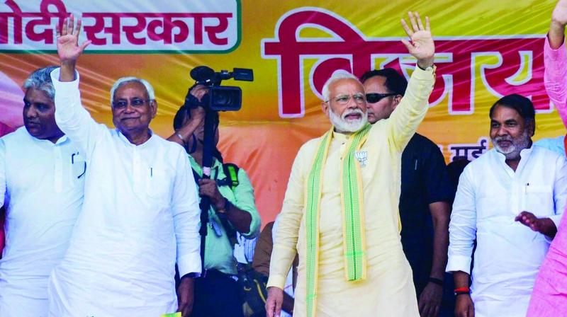 Prime Minister Narendra Modi and Bihar chief minister Nitish Kumar wave at crowd during an election rally in Buxar on Tuesday. (Photo: AP)