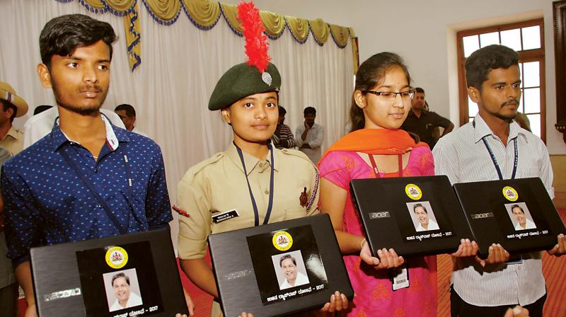 Students with the laptops distributed by the state government at Vidhana Soudha on Wednesday. (Photo: DC)
