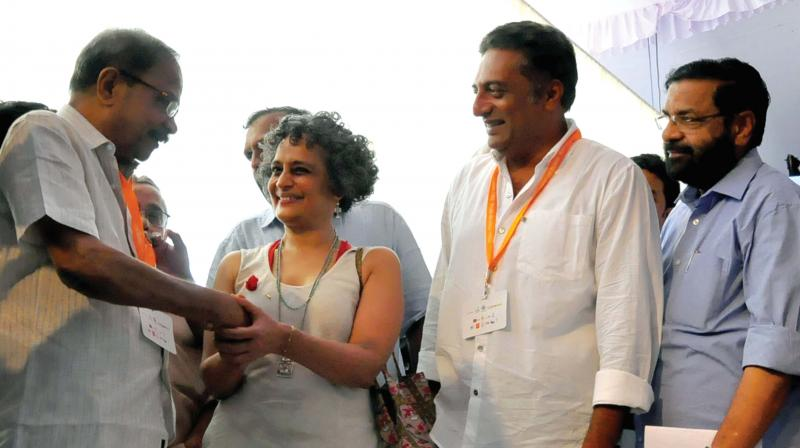 Writer Arundhati Roy greets writer M.T. Vasudevan Nair as actor Prakash Raj looks on, during the inaugural ceremony of Kerala Literature Festival in Kozhikode on Thursday. (Photo: DC)