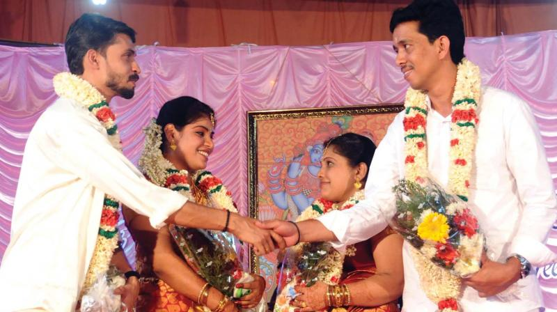 Biju and Suresh, who tied knot with Sreelakshmi and Radha, inmates of Kochi Corporation's Mahila Mandiram, greet each other after the marriage function on Friday. (Photo: ARUN CHANDRABOSE)