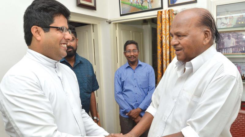 Perumbadavam Sreedharan is greeted by Fr Vincy Varghese, vice-principal of Mar Ivanios College, at the novelist's residence at Thamalam in Thiruvananthapuram on Monday. (Photo: Peethambaran Payyeri)
