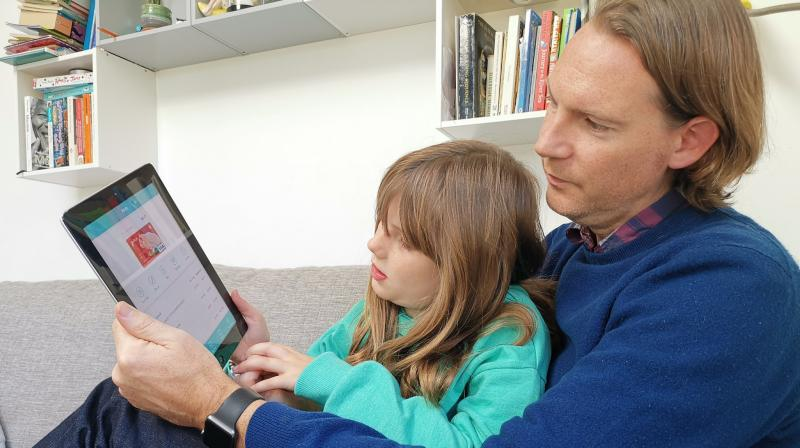 In this photo, Paddy Kelly and his daughter Ailish use Gohenry, one of a wave of digital banking apps for children, in London. (AP Photo/Kelvin Chan)