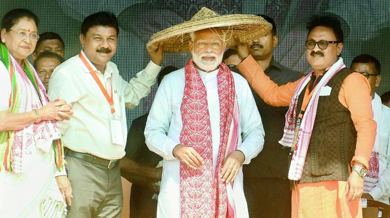Prime Minister Narendra Modi being presented an Assamese japi during an election rally, at Kendukona in Kamrup (Rural) district of Assam on Thursday.  (PTI)