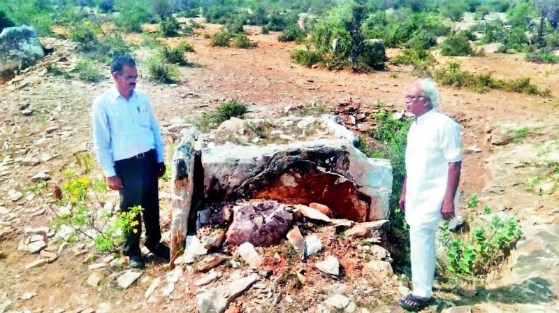 Archaeologist E. Sivanagi Reddy, and Durga temple trust board member Gudapati Padmasekhar inspect the dolmens at Tangeda village on Wednesday.