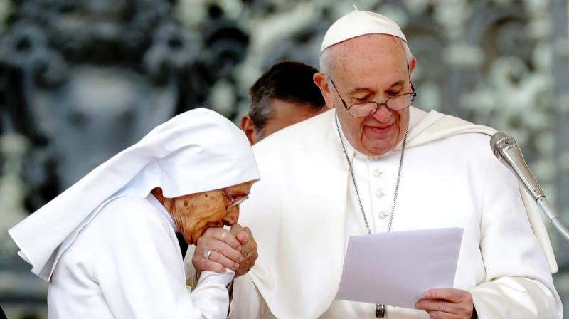While visiting a Catholic shrine in Loreto on Monday, Pope Franics repeatedly kept withdrawing his right hand as a long line of people bowed down and tried to kiss the ring on it. (Photo: AFP)