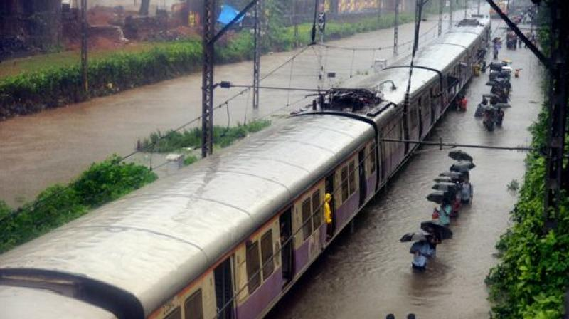 Commuters walk through rain waters along a local train after heavy rains lashed Mumbai on Tuesday.