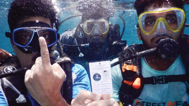 Youngsters sport the voter ID card given to them while scuba diving off the Netrani Islands in Uttara Kannada district – DC