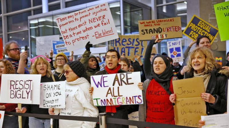 Faced with protests, Trump insists travel curbs not Muslim ban