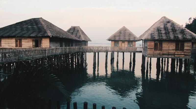 15 Telunas beach resort villas branch out on stilts over the water, resembling a local water village or kampung.