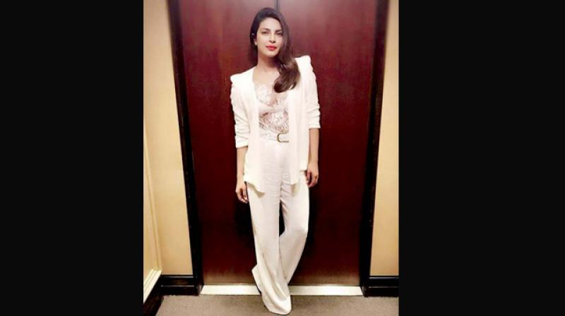 Priyanka Chopra pairs her trouser with a sheer top and a long jacket.